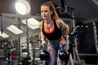 Young woman holding kettle bells in gym 11015327306  写真素材・ストックフォト・画像・イラスト素材 アマナイメージズ