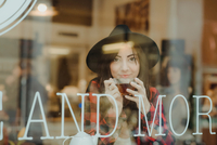 Portrait of young woman sitting in cafe, view through window 11015327545| 写真素材・ストックフォト・画像・イラスト素材|アマナイメージズ