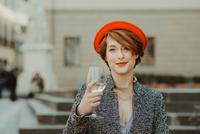 Portrait of young woman, outdoors, holding glass of wine 11015327547| 写真素材・ストックフォト・画像・イラスト素材|アマナイメージズ