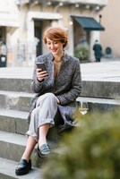 Young woman sitting on steps, using smartphone, glass of wine beside her 11015327548| 写真素材・ストックフォト・画像・イラスト素材|アマナイメージズ