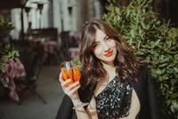 Portrait of young woman, outdoors, raising glass 11015327553| 写真素材・ストックフォト・画像・イラスト素材|アマナイメージズ