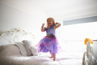 Young girl dressed in fairy costume, standing on bed, smiling 11015327597| 写真素材・ストックフォト・画像・イラスト素材|アマナイメージズ