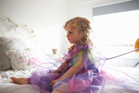 Young girl dressed in fairy costume, sitting on bed 11015327598| 写真素材・ストックフォト・画像・イラスト素材|アマナイメージズ