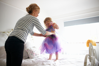 Young girl dressed in fairy costume, standing on bed, mother lifting her 11015327599| 写真素材・ストックフォト・画像・イラスト素材|アマナイメージズ