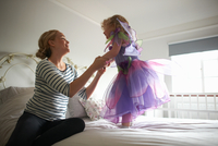 Young girl dressed in fairy costume, standing on bed, mother holding her hands 11015327600| 写真素材・ストックフォト・画像・イラスト素材|アマナイメージズ