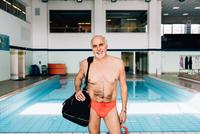 Senior man carrying bag by swimming pool 11015327709| 写真素材・ストックフォト・画像・イラスト素材|アマナイメージズ
