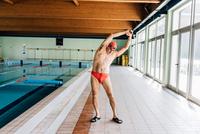 Senior man stretching by swimming pool 11015327713  写真素材・ストックフォト・画像・イラスト素材 アマナイメージズ
