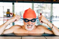Senior man pulling mean face wearing goggles in swimming pool 11015327731| 写真素材・ストックフォト・画像・イラスト素材|アマナイメージズ