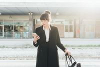 Businesswoman using mobile phone in train station, Milan, Italy 11015327763| 写真素材・ストックフォト・画像・イラスト素材|アマナイメージズ