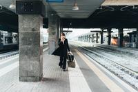 Businesswoman using mobile phone in train station, Milan, Italy 11015327764| 写真素材・ストックフォト・画像・イラスト素材|アマナイメージズ