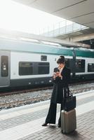 Businesswoman using mobile phone in train station, Milan, Italy 11015327765| 写真素材・ストックフォト・画像・イラスト素材|アマナイメージズ