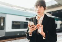 Businesswoman using mobile phone in train station, Milan, Italy 11015327766| 写真素材・ストックフォト・画像・イラスト素材|アマナイメージズ