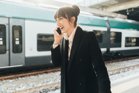 Businesswoman using mobile phone in train station, Milan, Italy 11015327767| 写真素材・ストックフォト・画像・イラスト素材|アマナイメージズ