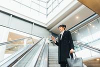 Businesswoman using mobile phone on escalator, Milan, Italy 11015327768| 写真素材・ストックフォト・画像・イラスト素材|アマナイメージズ
