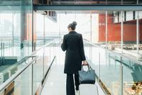 Businesswoman using mobile and pulling trolley luggage, Milan, Italy 11015327769| 写真素材・ストックフォト・画像・イラスト素材|アマナイメージズ