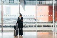 Businesswoman using mobile phone, Milan, Italy 11015327770| 写真素材・ストックフォト・画像・イラスト素材|アマナイメージズ
