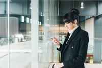 Businesswoman using mobile phone, Milan, Italy 11015327771| 写真素材・ストックフォト・画像・イラスト素材|アマナイメージズ
