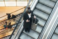 Businesswoman using mobile phone on escalator, Milan, Italy 11015327773| 写真素材・ストックフォト・画像・イラスト素材|アマナイメージズ
