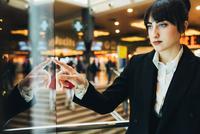 Businesswoman looking at shop window, Milan, Italy 11015327775| 写真素材・ストックフォト・画像・イラスト素材|アマナイメージズ
