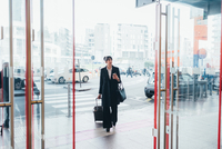 Businesswoman pulling trolley luggage into building, Milan, Italy 11015327776| 写真素材・ストックフォト・画像・イラスト素材|アマナイメージズ