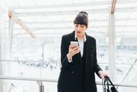 Businesswoman using mobile phone on business trip, Milan, Italy 11015327777| 写真素材・ストックフォト・画像・イラスト素材|アマナイメージズ