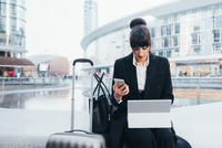 Businesswoman with trolley luggage using mobile phone and digital tablet, Milan, Italy 11015327779| 写真素材・ストックフォト・画像・イラスト素材|アマナイメージズ