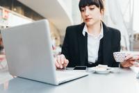 Businesswoman using laptop in coffee shop, Milan, Italy 11015327780| 写真素材・ストックフォト・画像・イラスト素材|アマナイメージズ