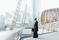 Businesswoman with trolley luggage on pedestrian bridge, Milan, Italy 11015327783| 写真素材・ストックフォト・画像・イラスト素材|アマナイメージズ
