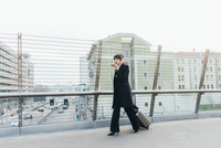 Businesswoman using mobile and pulling trolley luggage, Milan, Italy 11015327786  写真素材・ストックフォト・画像・イラスト素材 アマナイメージズ