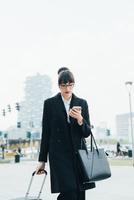 Businesswoman using mobile and pulling trolley luggage, Milan, Italy 11015327789  写真素材・ストックフォト・画像・イラスト素材 アマナイメージズ