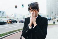 Businesswoman blowing nose on busy road, Milan, Italy 11015327790| 写真素材・ストックフォト・画像・イラスト素材|アマナイメージズ
