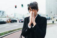Businesswoman blowing nose on busy road, Milan, Italy 11015327790  写真素材・ストックフォト・画像・イラスト素材 アマナイメージズ