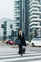 Businesswoman using mobile and pulling trolley luggage, Milan, Italy 11015327791| 写真素材・ストックフォト・画像・イラスト素材|アマナイメージズ