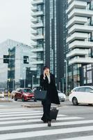 Businesswoman using mobile and pulling trolley luggage, Milan, Italy 11015327791  写真素材・ストックフォト・画像・イラスト素材 アマナイメージズ