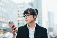 Businesswoman using mobile, Milan, Italy 11015327792| 写真素材・ストックフォト・画像・イラスト素材|アマナイメージズ