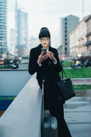 Businesswoman with trolley luggage using mobile waiting by wall, Milan, Italy 11015327793| 写真素材・ストックフォト・画像・イラスト素材|アマナイメージズ