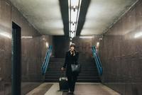 Businesswoman using mobile and pulling trolley luggage, Milan, Italy 11015327794| 写真素材・ストックフォト・画像・イラスト素材|アマナイメージズ