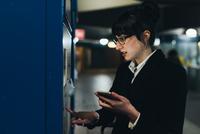 Businesswoman using ticket machine, Milan, Italy 11015327795| 写真素材・ストックフォト・画像・イラスト素材|アマナイメージズ