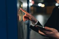 Businesswoman using ticket machine, Milan, Italy 11015327796| 写真素材・ストックフォト・画像・イラスト素材|アマナイメージズ