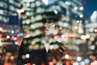 Businesswoman using mobile phone behind glass reflection of buildings, Milan, Italy 11015327801| 写真素材・ストックフォト・画像・イラスト素材|アマナイメージズ