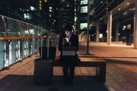 Businesswoman with trolley luggage using digital tablet, Milan, Italy 11015327804| 写真素材・ストックフォト・画像・イラスト素材|アマナイメージズ