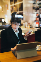 Businesswoman using mobile phone and digital tablet in cafe 11015327808| 写真素材・ストックフォト・画像・イラスト素材|アマナイメージズ