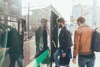 Two young men boarding tram  at city tram station 11015327828  写真素材・ストックフォト・画像・イラスト素材 アマナイメージズ