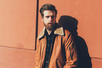 Portrait of cool young bearded man leaning against orange wall 11015327829  写真素材・ストックフォト・画像・イラスト素材 アマナイメージズ