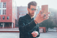 Cool young male hipster taking smartphone selfie in city 11015327830| 写真素材・ストックフォト・画像・イラスト素材|アマナイメージズ