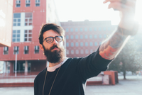 Cool young male hipster taking smartphone selfie in city 11015327831| 写真素材・ストックフォト・画像・イラスト素材|アマナイメージズ