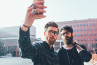 Two cool young male hipsters taking smartphone selfie in city 11015327832| 写真素材・ストックフォト・画像・イラスト素材|アマナイメージズ