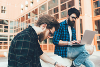 Two young male hipsters sitting on wall typing on laptop 11015327833| 写真素材・ストックフォト・画像・イラスト素材|アマナイメージズ