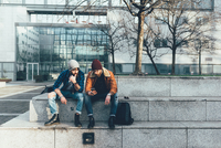 Two young male hipsters sitting on wall looking at smartphone 11015327836| 写真素材・ストックフォト・画像・イラスト素材|アマナイメージズ