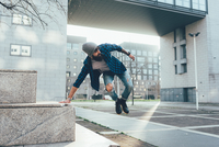 Young male hipster jumping mid air practicing parkour in city 11015327837| 写真素材・ストックフォト・画像・イラスト素材|アマナイメージズ